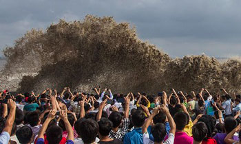 In the moment… snap-happy onlookers taking pictures of tidal waves after a typhoon in China. | Chance Chan / Reuters