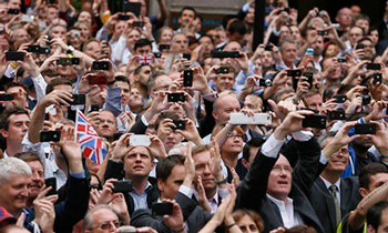 Spectators taking pictures of the British team's celebration parade after the London 2012 Olympics. | AFP / Getty Images
