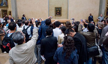Tourists photographing the Mona Lisa in the Louvre in Paris. | Imagebroker / Alamy