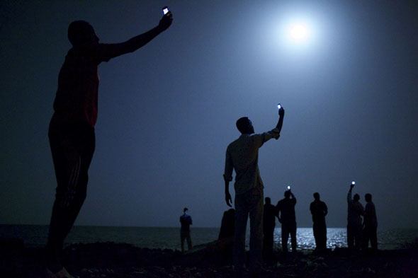 John Stanmeyer took this photograph for National Geographic of African migrants near Djibouti city, raising their phones in an attempt to capture an inexpensive signal from neighboring Somalia. It won the World Press Photo of the Year award. | John Stanmeyer / VII for National Geographic