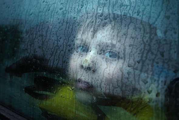 I was about to go to a shop with my nephew on a rainy day. I got out of my parked car first and then realized that all the windows had fogged up. I saw a great photo opportunity. Since I had my camera right there, I asked my nephew to stay inside, while I take a couple of photos. He pressed his nose against the window, as he waited and, I had an image out of seemingly nothing. | EyeVoyage