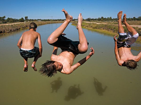 Three Boys in Midair -- Young men jump off a bridge into the Mulwala Canal in Deniliquin, Australia. | Amy Toensing / National Geographic