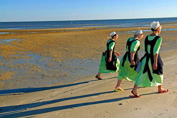 Amish Women on Beach -- Amish women walk on a beach in Waveland, Mississippi. | Johnny Nicoloro / National Geographic