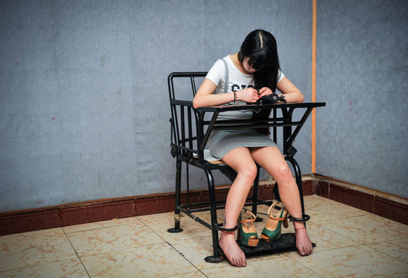 World Press Photo 2014 -- Portraits	, 2nd prize	singles, Liu Song: Accused -- A woman suspected of engaging in illegal sex trade is held for questioning at a police station.