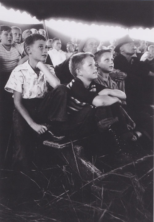 Cover the top of this image with your hand. Look at it for 10-15 seconds.  Get used to the tones of the children's faces.  Now remove your hand.  See how the glowing light jumps out at you.  Its too strong of a value shift in a part of the picture that has no importance. Indiana, 1949. | Robert Capa