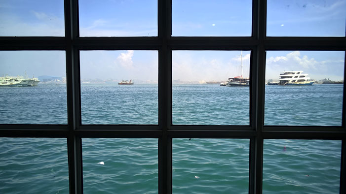 A window with a view -- smoldering rubbish island of Tilafushi in the background | Nokia Lumia 830 / Daniel Kestenholz